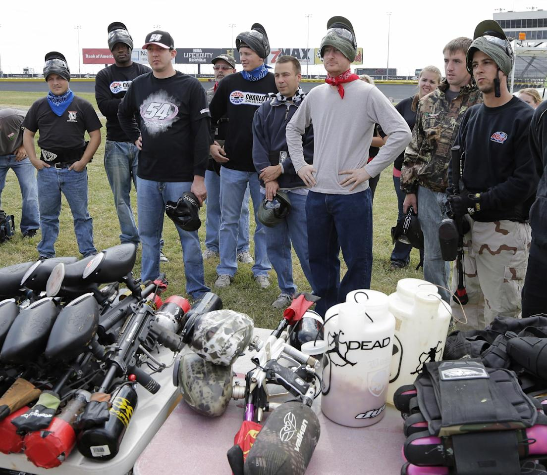 NASCAR driver Kyle Busch, third from left, listens with the teams as they receive the rules for a paintball game against members of the media at Charlotte Motor Speedway in Concord, N.C., Tuesday, Sept. 24, 2013, promoting the upcoming Bank of America 500 NASCAR Sprint Cup auto race on Oct. 12, 2013. (AP Photo/Chuck Burton)