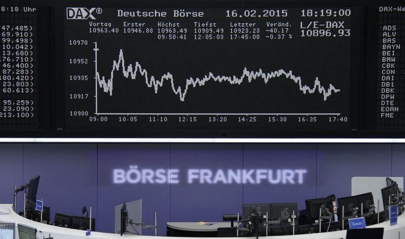 A trader is working at his desk in front of the DAX board at the Frankfurt stock exchange