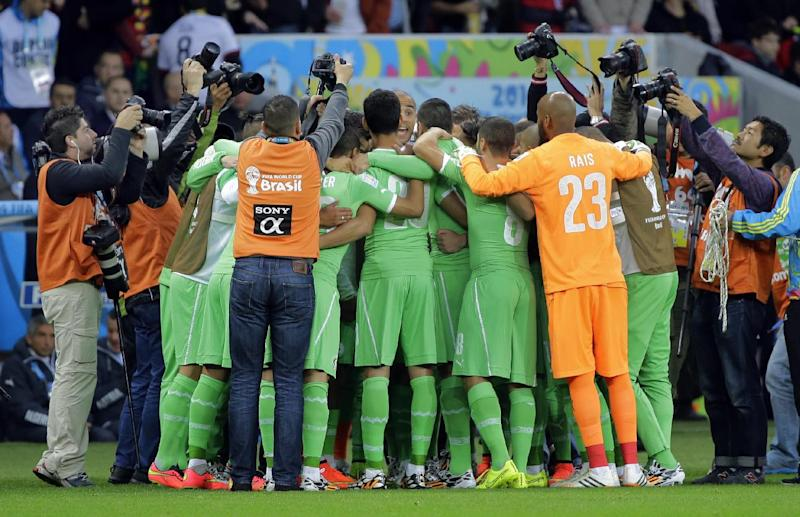 Photographers crowd around the Algerian team as they form a huddle before the World Cup round of 16 soccer match between Germany and Algeria at the Estadio Beira-Rio in Porto Alegre, Brazil, Monday, June 30, 2014