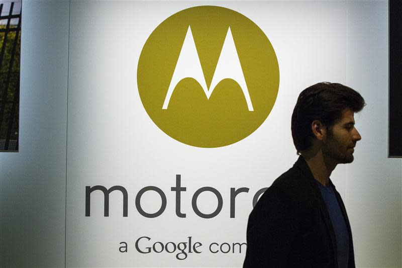 A man walks past a Motorola logo at a launch event for Motorola's new Moto X phone in New York