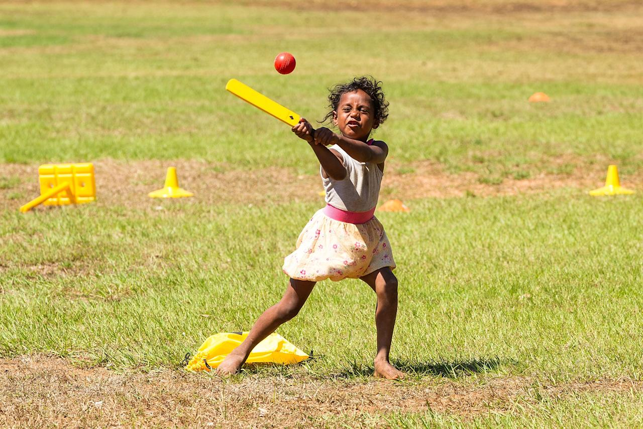DARWIN, AUSTRALIA - AUGUST 10: A young girl plays cricket during a visit by the Australian cricket team to Pirlangimpi of the Tiwi Islands on August 10, 2012 on the Tiwi Islands, Australia.  (Photo by Mark Nolan/Getty Images)