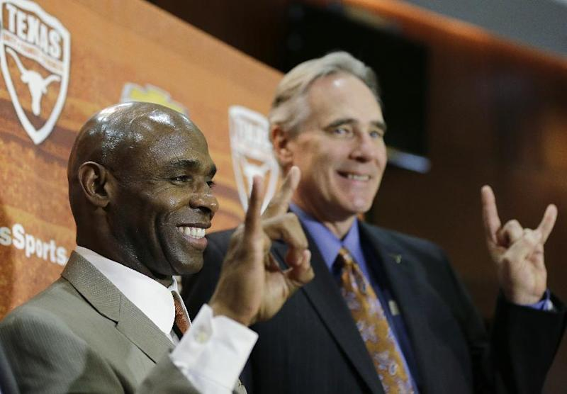 "New Texas football Charlie Strong, left, poses for a photo with athletic director Steve Patterson, right, both displaying the ""Hook 'em Horns"" sign, following an NCAA college news conference announcing Strong's hire, Monday, Jan. 6, 2014, in Austin, Texas. Strong replaces Mack Brown, who coached Texas for 16 years and won the 2005 national championship. Strong spent the previous four years at Louisville"