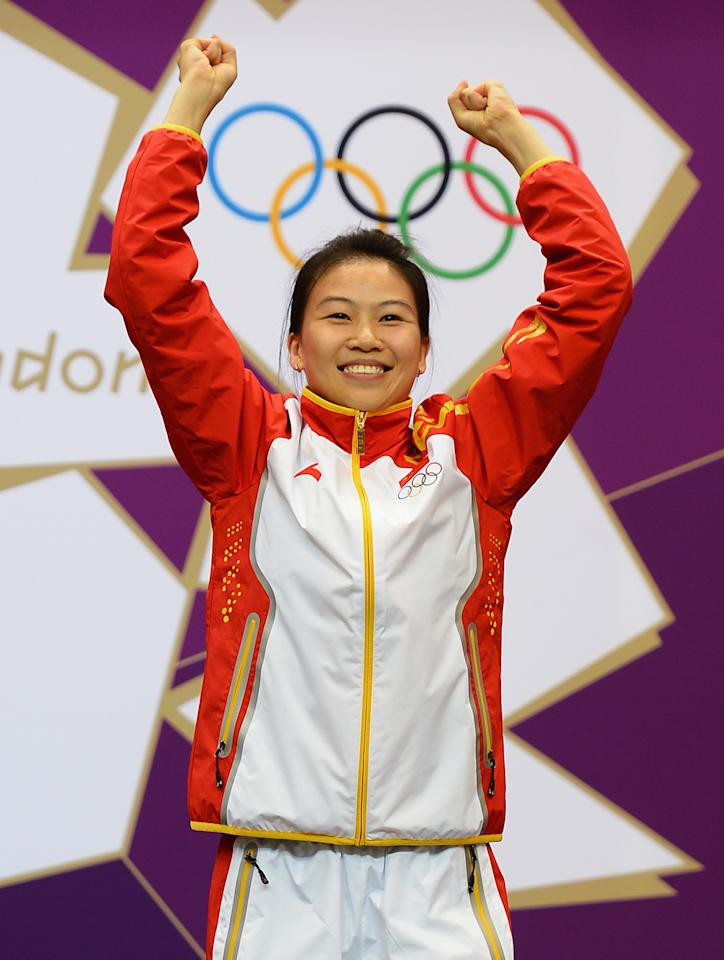 Gold medalist Siling Yi of China celebrates winning the first gold medal of the London Games. She won the Women's 10m Air Rifle Shooting Final on Day 1 of the London 2012 Olympic Games at The Royal Artillery Barracks on July 28, 2012 in London, England.  Sylwia Bogacka of Poland won silver and Dan Yu of China won bronze.  (Photo by Lars Baron/Getty Images)