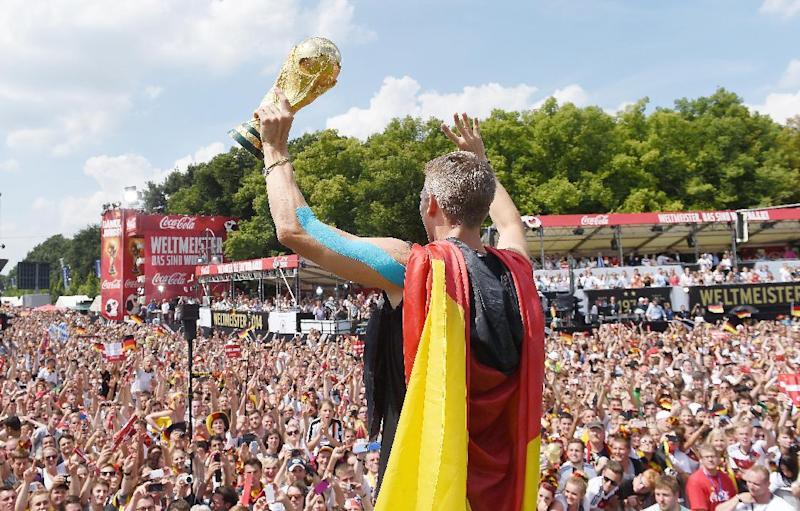 Bastian Schweinsteiger cheers celebrates Germany's victory in the World Cup at Berlin's Brandenburg Gate on July 15, 2014
