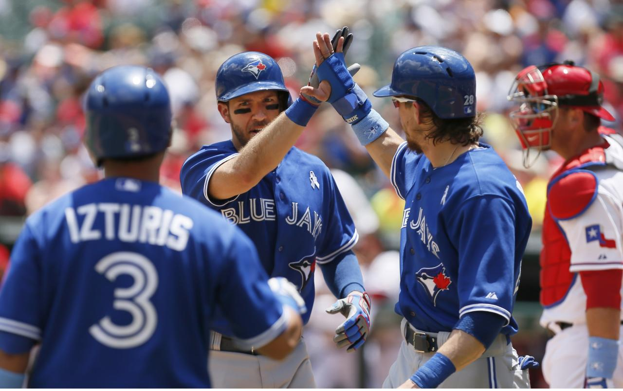ARLINGTON, TX - JUNE 16: J.P. Arencibia #9 of the Toronto Blue Jays, center, is congratulated by teammates Colby Rasmus #28 and Maicer Izturis #3 after hitting a two-run home run to left field in the second inning of a baseball game against the Texas Rangers at Rangers Ballpark in Arlington on June 16, 2013 in Arlington, Texas. (Photo by Brandon Wade/Getty Images)