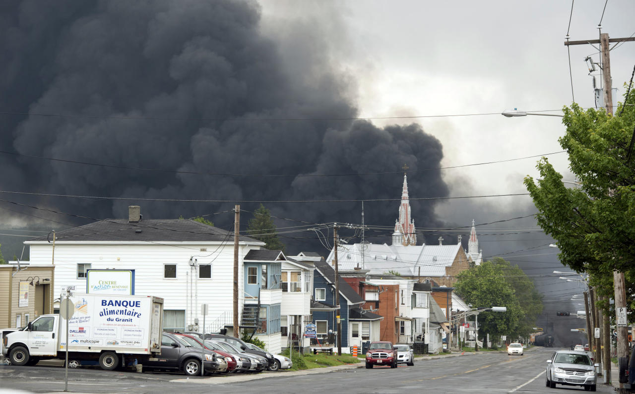 Smoke rises from railway cars that were carrying crude oil after derailing in downtown Lac Megantic, Quebec, Canada, Saturday, July 6, 2013. The derailment sparked several explosions and forced the evacuation of up to 1,000 people. (AP Photo/The Canadian Press, Paul Chiasson)