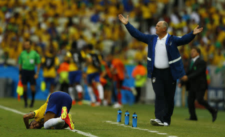 Brazil's coach Luiz Felipe Scolari reacts as Neymar lies on the pitch after a challenge during their 2014 World Cup Group A soccer match against Mexico at the Castelao arena in Fortaleza