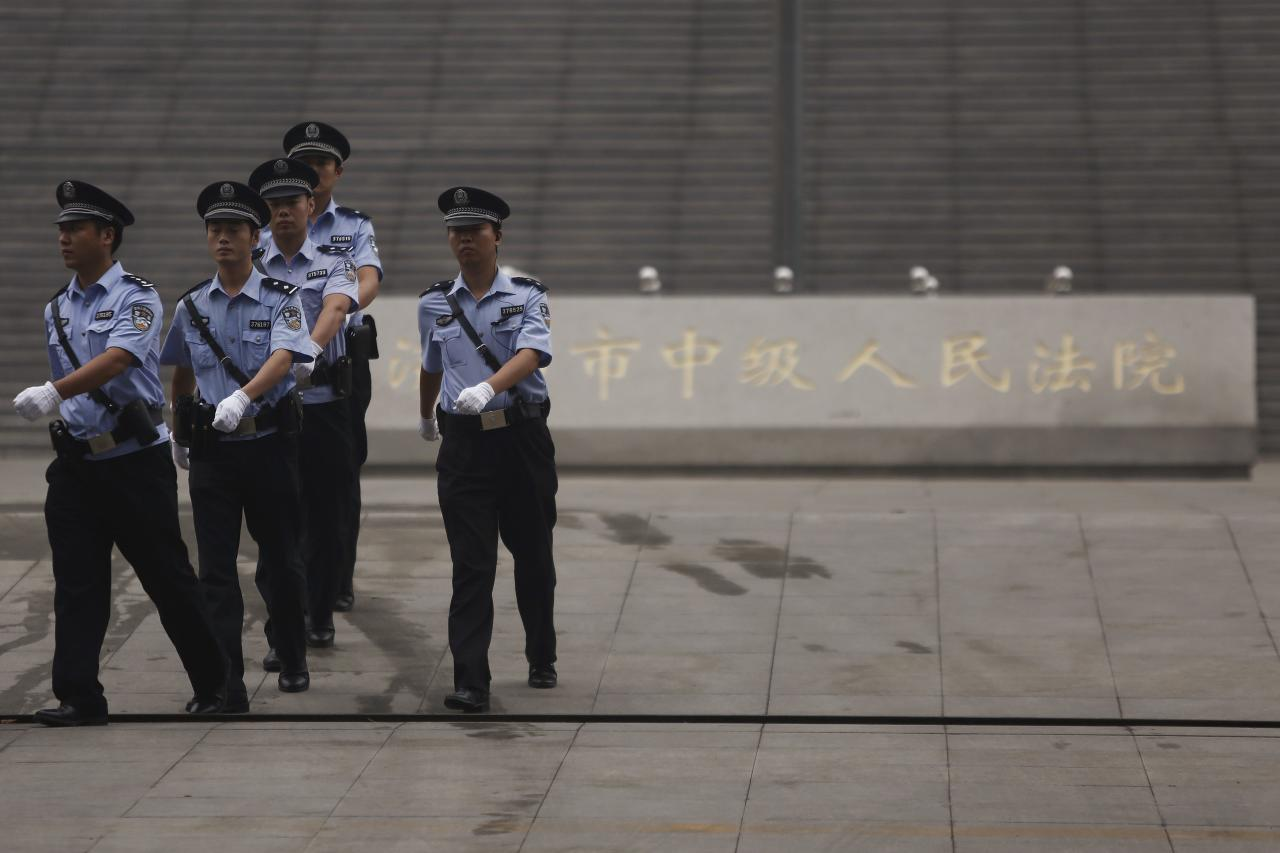 Policemen patrol near the entrance of the Jinan Intermediate People's Court where the trial of disgraced Chinese politician Bo Xilai will be held, in Jinan, Shandong province September 22, 2013. A Chinese court will announce its verdict on former top politician Bo on Sunday following his 5-day trial last month on charges of corruption and abuse of power. He could be handed a long jail term by the Communist Party-controlled court. REUTERS/Aly Song (CHINA - Tags: POLITICS CRIME LAW)