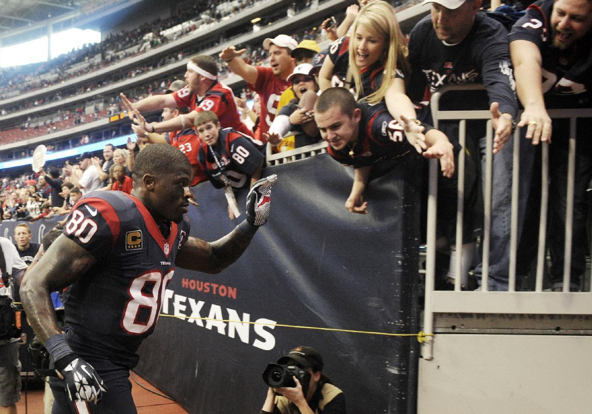 Houston Texans' Andre Johnson (80) slaps hands with fans as he runs off the field after an NFL football game against the Jacksonville Jaguars, Sunday, Nov. 18, 2012, in Houston. Johnson scored the winning touchdown in overtime to defeat the Jaguars 43-37. (AP Photo/Dave Einsel)