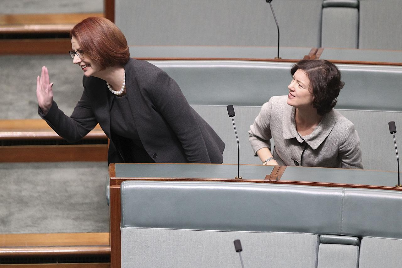 CANBERRA, AUSTRALIA - JUNE 27: Former PM Julia Gillard (L) waves as she sits next to Kirsten Livermore in the House of Representatives on June 27, 2013 in Canberra, Australia. Kevin Rudd won an Australian Labor Party leadership ballot 57-45 last night, and will be sworn in this morning as Australian Prime Minister by Governor-General Quentin Bryce. Rudd was Prime Minister from 2007 to 2010 before he was dumped by his party for his deputy Julia Gillard. Gillard has announced that she will leave parliament and not contest her seat following her ballot loss. (Photo by Stefan Postles/Getty Images)