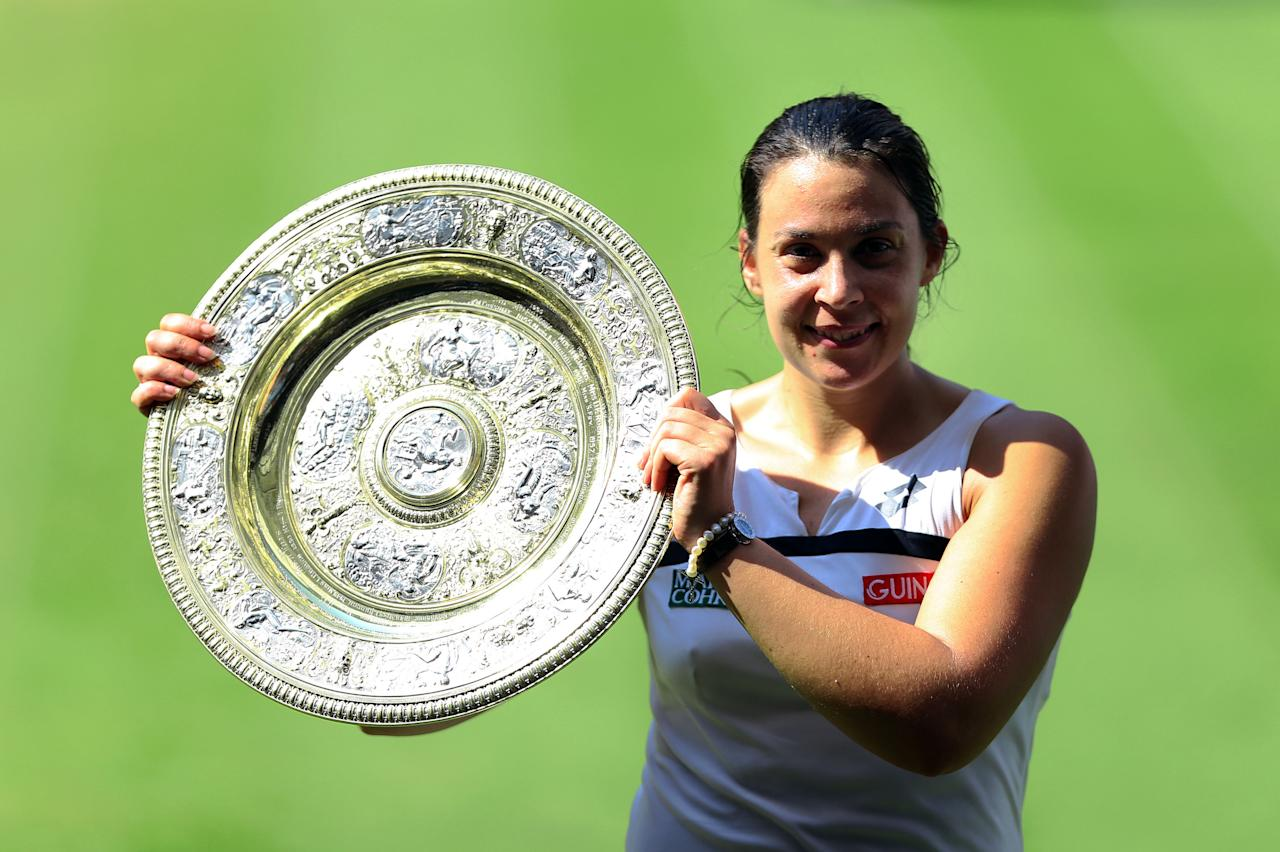 France's Marion Bartoli with the trophy after beating Germany's Sabine Lisicki during day twelve of the Wimbledon Championships at The All England Lawn Tennis and Croquet Club, Wimbledon.