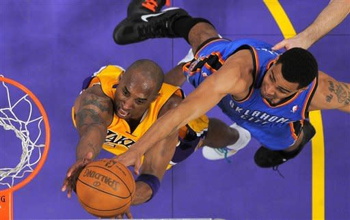 Los Angeles Lakers guard Kobe Bryant, left, goes after a rebound with Oklahoma City Thunder guard Thabo Sefolosha of Switzerland during the first half in Game 3 of an NBA basketball playoffs Western Conference semifinal, Friday, May 18, 2012, in Los Angeles.  (AP Photo/Mark J. Terrill)