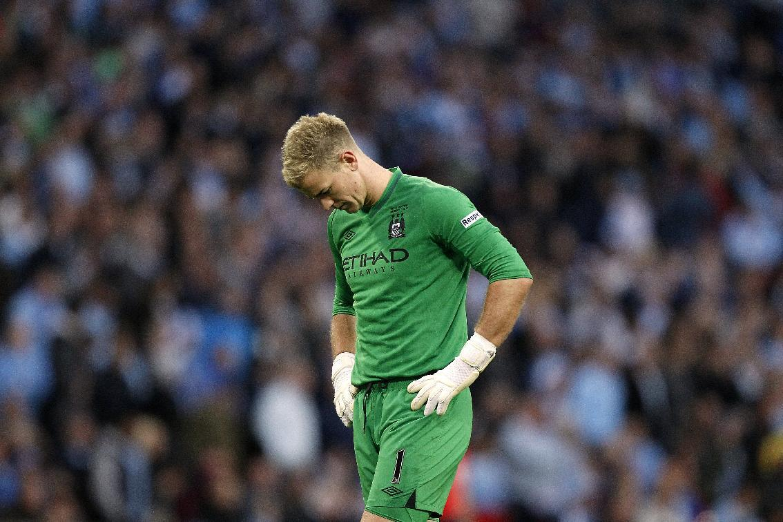Manchester City goalkeeper Joe Hart stands dejected after conceding the winning goal, scored by Wigan Athletic's Ben Watson
