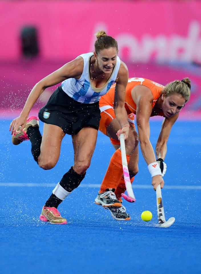 LONDON, ENGLAND - AUGUST 10:  Luciana Aymar #8 of Argentina battles for the ball against Eva De Goede #24 of Netherlands during the first half of the Women's Hockey gold medal match on Day 14 of the London 2012 Olympic Games at Hockey Centre on August 10, 2012 in London, England.  (Photo by Mike Hewitt/Getty Images)