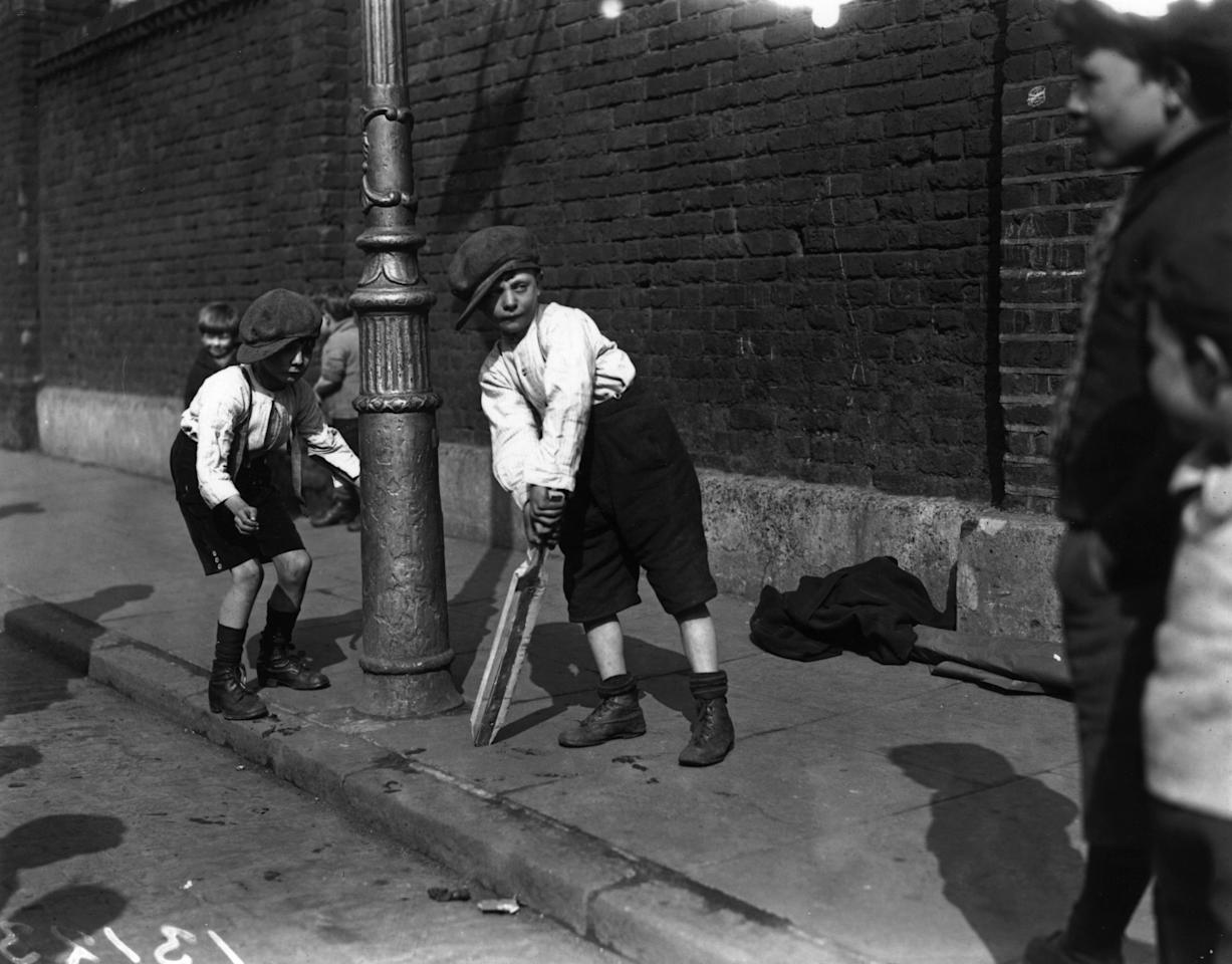 Young boys playing cricket in a street in London's East End.   (Photo by Fox Photos/Getty Images)