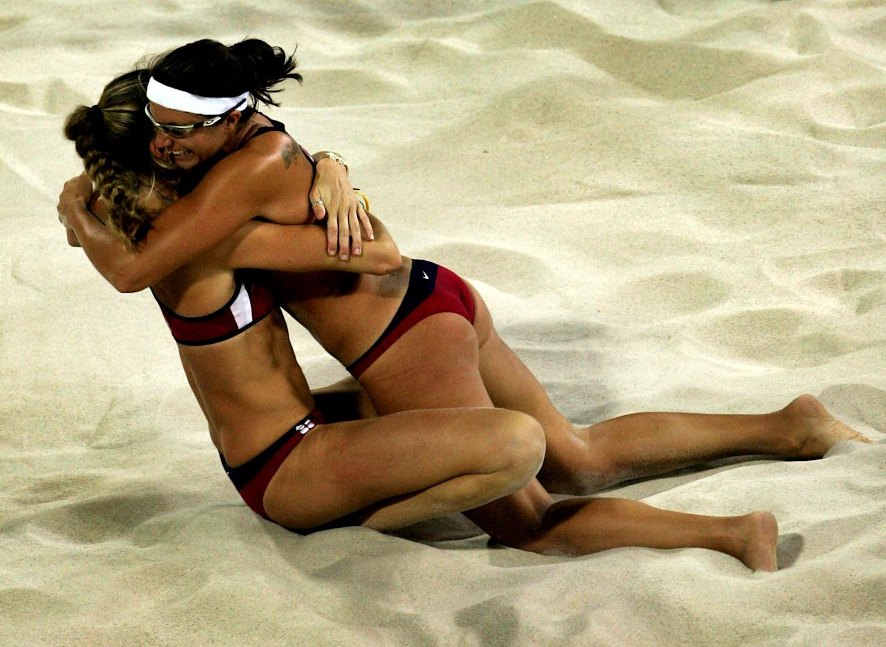 ATHENS - AUGUST 24:  Kerri Walsh and Misty May (R) from the United States celebrate their win in the women's gold medal match on August 24, 2004 during the Athens 2004 Summer Olympic Games at the Olympic Beach Volleyball Centre at the Faliro Coastal Zone Complex in Athens, Greece. (Photo by Ian Waldie/Getty Images)