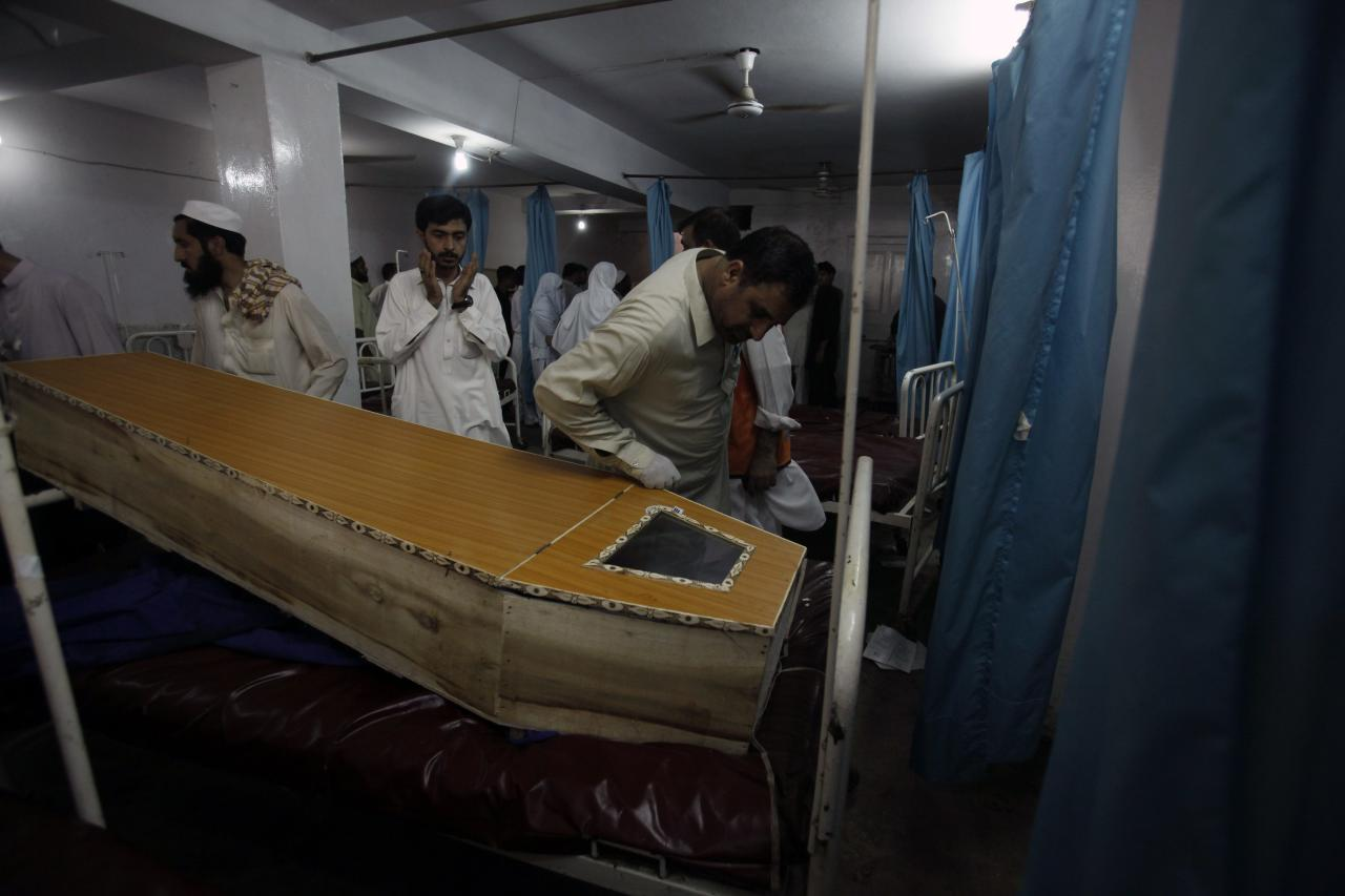 People stand near the coffin of a victim, who was killed in a bomb blast, at a hospital in Peshawar September 29, 2013. Twin blasts in the northwestern Pakistan city of Peshawar killed 33 people and wounded 70 on Sunday, a week after two bombings at a church in the frontier city killed scores, police and hospital authorities said.REUTERS/ Fayaz Aziz (PAKISTAN - Tags: POLITICS CIVIL UNREST CRIME LAW)
