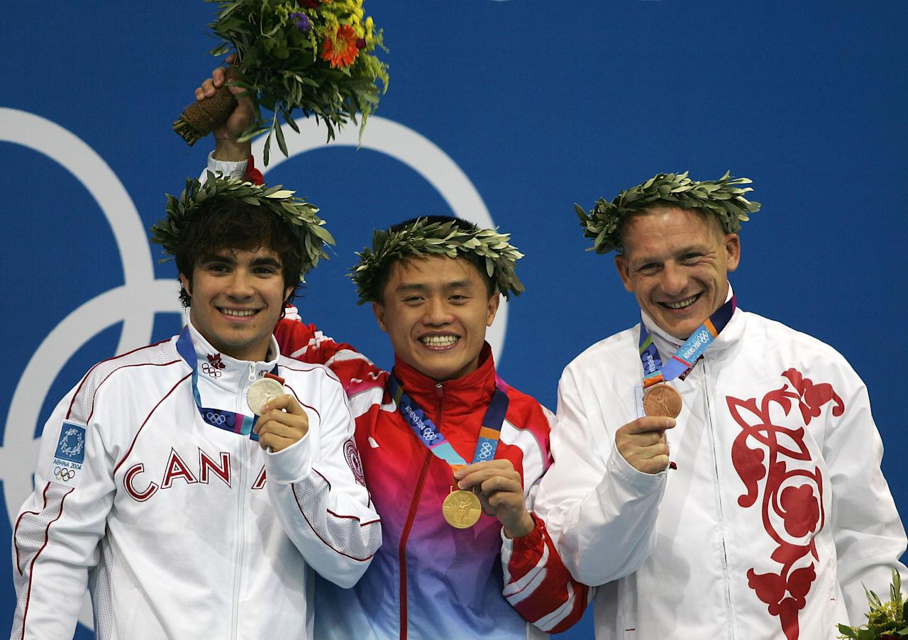 ATHENS - AUGUST 24: (L-R) Alexandre Despatie of Canada (Silver), Bo Peng of China (Gold) and Dmitri Sautin of Russia (Bronze) show their medals at the men's diving 3 metre springboard medal ceremony on August 24, 2004 during the Athens 2004 Summer Olympic Games at the Aquatic Centre Indoor Pool at the Olympic Sports Complex in Athens, Greece. (Photo by Daniel Berehulak/Getty Images for FINA)