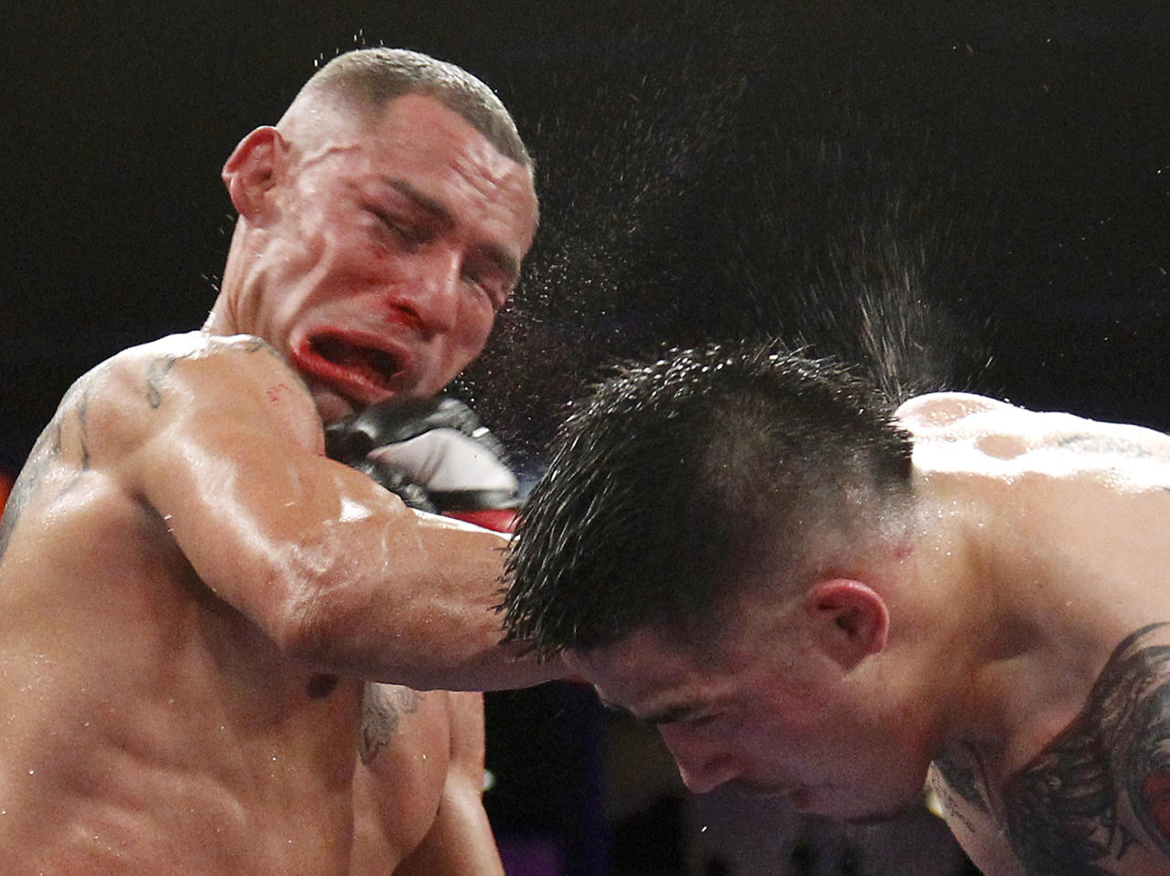 Brandon Rios (R) of the U.S. connects to the face with a punch on compatriot Mike Alvarado during the sixth round of their WBO Latino Super Lightweight Title boxing match in Carson, California October 13, 2012. Rios won by TKO in the seventh round. REUTERS/Danny Moloshok (UNITED STATES - Tags: SPORT BOXING TPX IMAGES OF THE DAY)