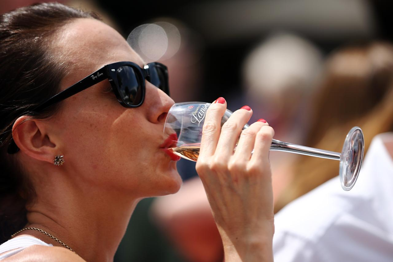 LONDON, ENGLAND - JUNE 25: A lady drinks champagne on day two of the Wimbledon Lawn Tennis Championships at the All England Lawn Tennis and Croquet Club on June 25, 2013 in London, England. (Photo by Dan Kitwood/Getty Images)