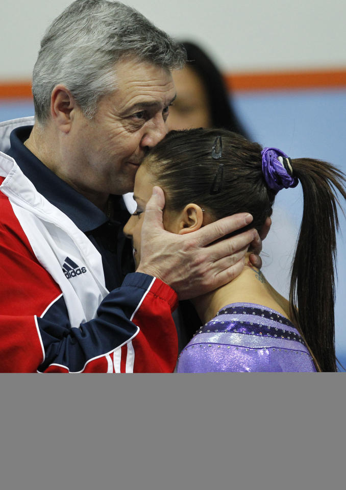 *RETRANSMISSION TO ADD ADDITIONAL INFORMATION* Gold medallist Alicia Sacramone of the U.S., right, is congratulated by a coach Mihai Brestyan of the U.S. team after her performance during the women's vault final of the World Championships Gymnastics in Rotterdam, Netherlands, Saturday Oct. 23, 2010.