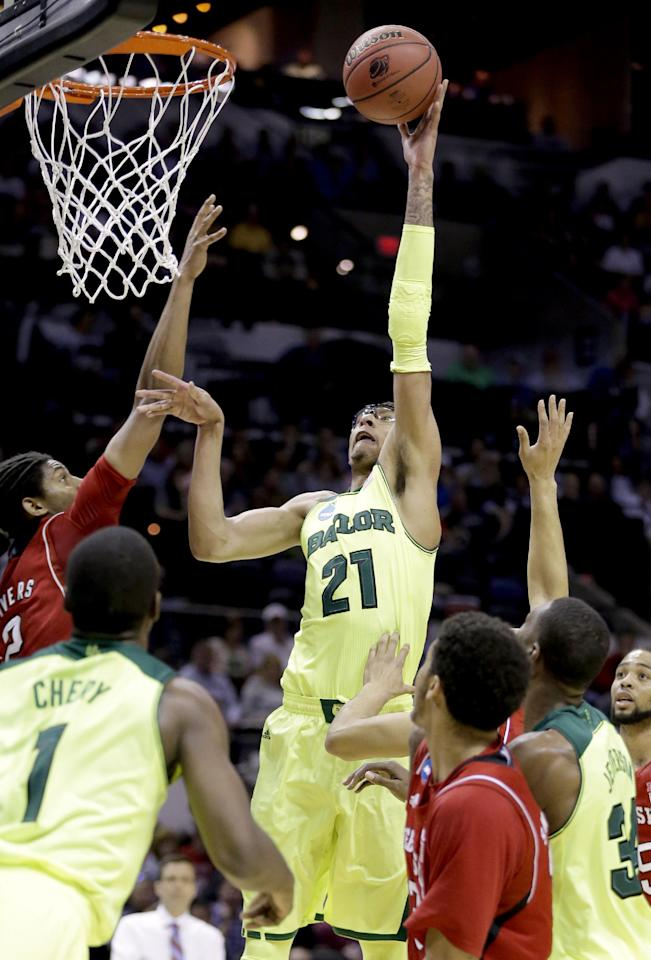 Baylor's Isaiah Austin (21) shoots as Nebraska's David Rivers, left, defends during the first half of a second-round game in the NCAA college basketball tournament Friday, March 21, 2014, in San Antonio. (AP Photo/Eric Gay)