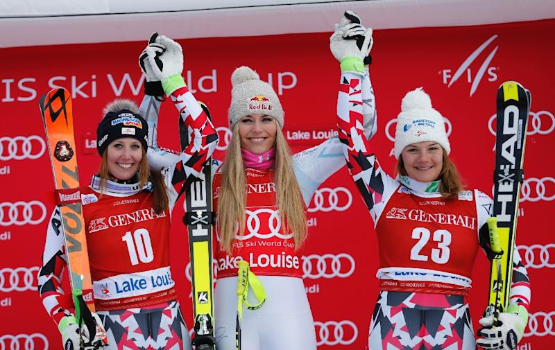 (L-R) Runner-up Corneila Huetter, winner Lindsey Vonn and third-placed Ramona Siebenhofer celebrate on the podium at the downhill Ski World Cup 2015-2016 at Lake Louise, Alberta on December 4, 2015