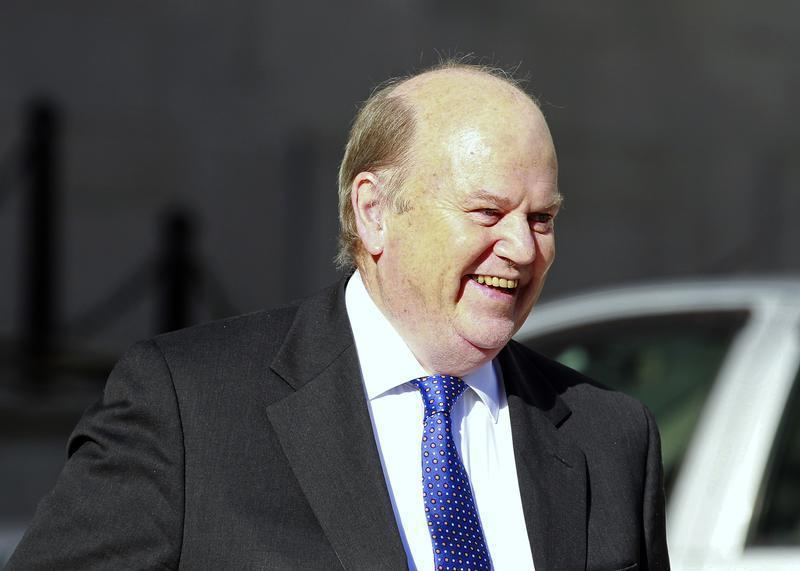 Ireland's Finance Minister Michael Noonan smiles as he arrives at the Government Buildings before presenting his budget to parliament in Dublin