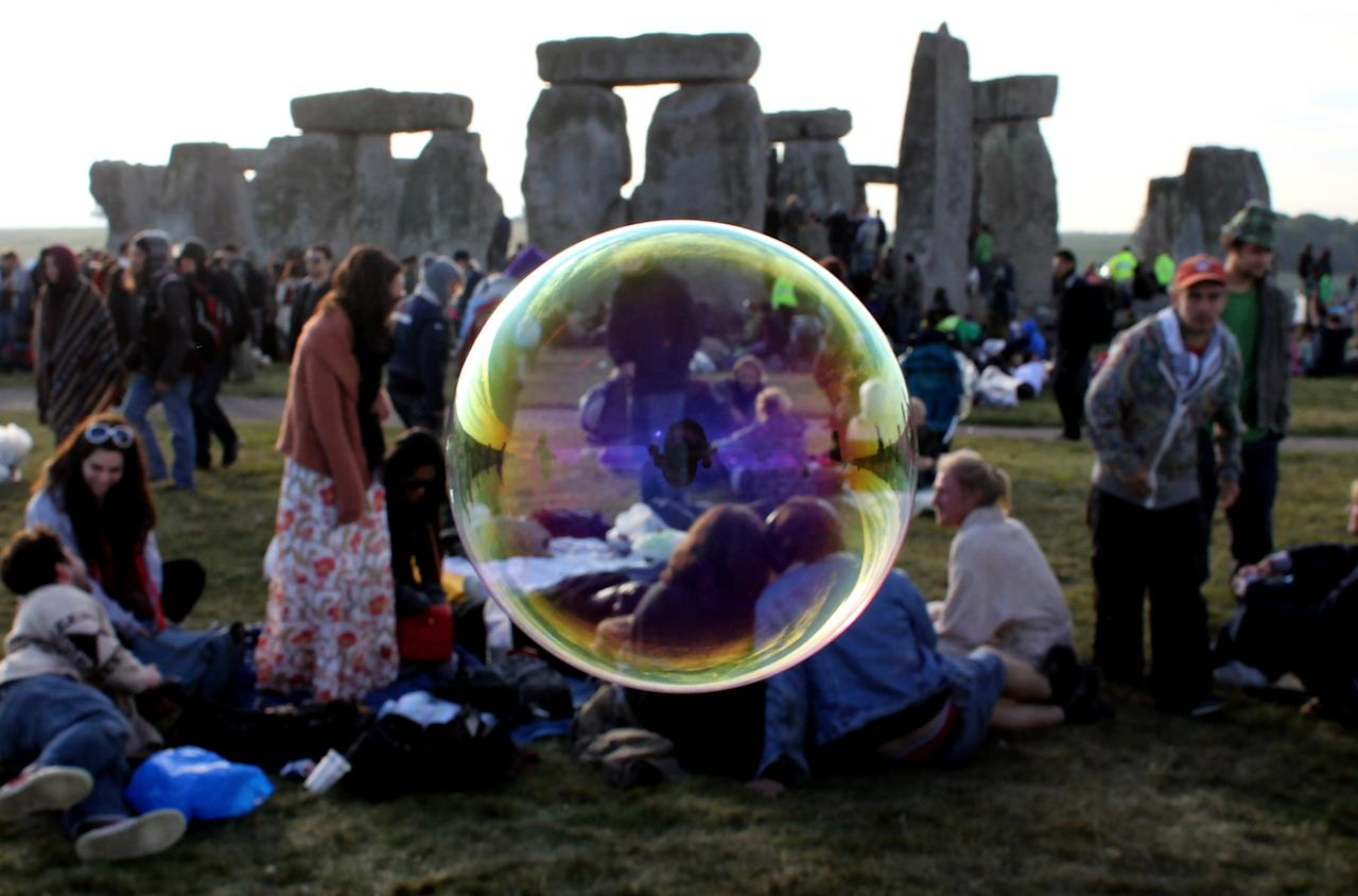 Bubbles float past as revellers watch as the midsummer sun rises just after dawn over the megalithic monument of Stonehenge on June 21, 2010 on Salisbury Plain, England. Thousands of revellers gathered at the 5,000 year old stone circle to see the sunrise on the Summer Solstice, which is the longest day of the year in the Northern Hemisphere. (Photo by Matt Cardy/Getty Images)
