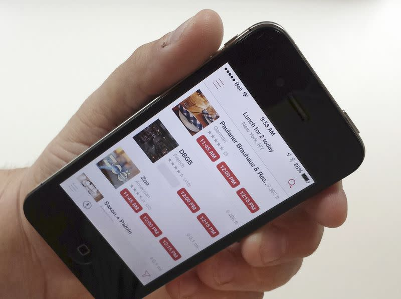 A man holds a smartphone displaying the OpenTable app in Toronto