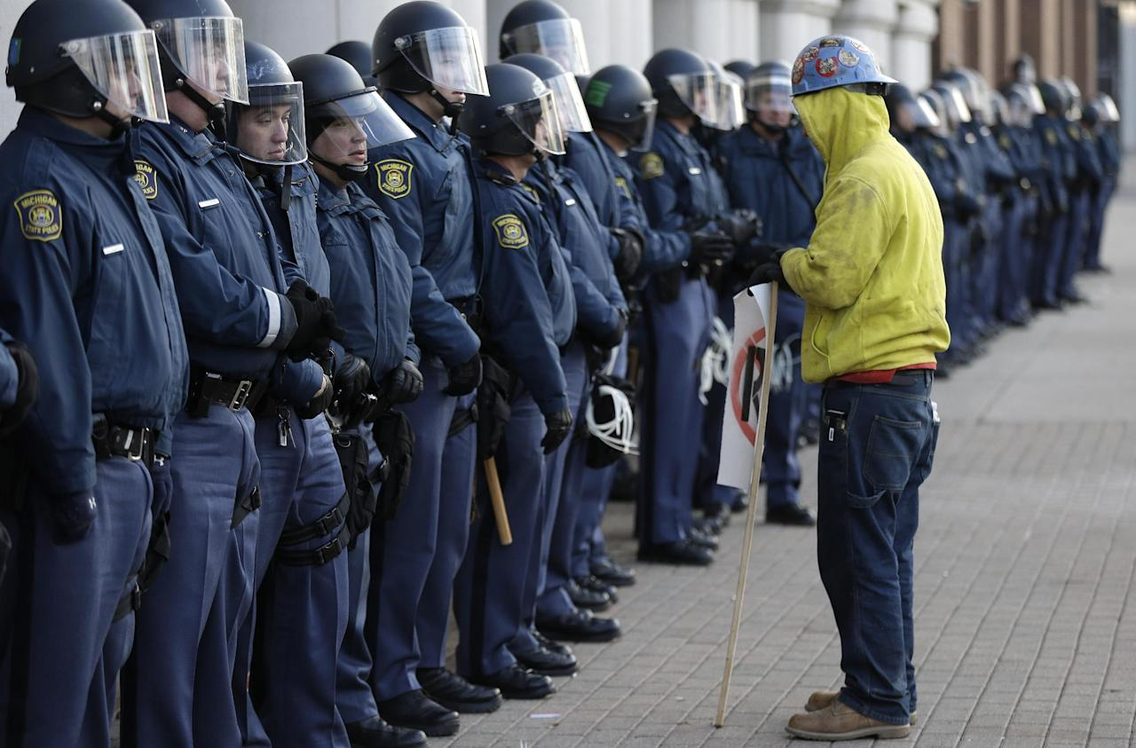 Protester Blake Nance, of Detroit, stands by a line of Michigan State Police guarding the George W. Romney State Building, where Gov. Snyder has an office in Lansing, Mich., Tuesday, Dec. 11, 2012. The crowd is protesting right-to-work legislation passed last week. Michigan could become the 24th state with a right-to-work law next week. Rules required a five-day wait before the House and Senate vote on each other's bills; lawmakers are scheduled to reconvene Tuesday and Gov. Snyder has pledged to sign the bills into law. (AP Photo/Paul Sancya)