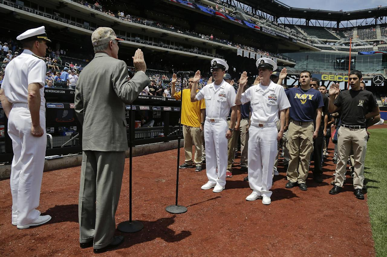 United States Sec. of the Navy Ray Mabus, second from left, swears in personnel from the different branches of the military during a re-enlistment ceremony at Citi Field before the start of a baseball game between the Pittsburgh Pirates and New York Mets, Monday, May 26, 2014, in New York. (AP Photo/Julie Jacobson)