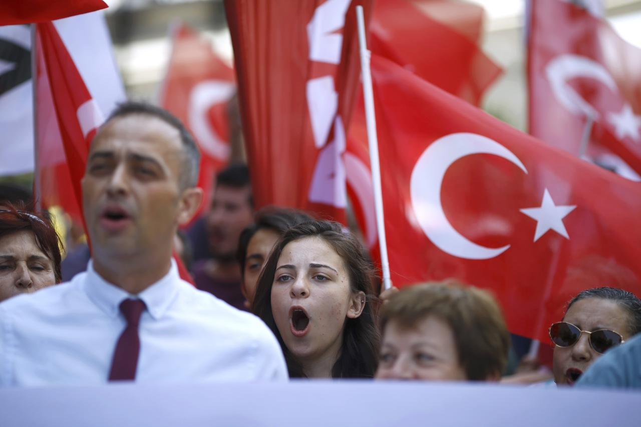 Demonstrators wave Turkish flags as they shout slogans demanding the extradition of U.S.-based cleric Fethullah Gulen, whom the Turkish government blame for a failed coup attempt last week, during a protest near the U.S. Embassy in Ankara, Turkey, July 19, 2016. REUTERS/Osman Orsal