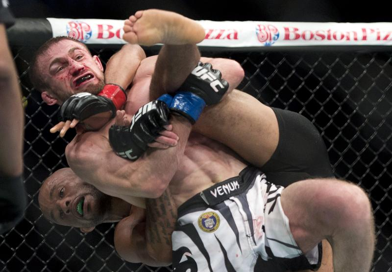 Demetrious Johnson, of the United States, throws Ali Bagautinov, of Russia, to the mat during the flyweight bout at UFC 174 in Vancouver, British Columbia, Saturday, June, 14, 2014
