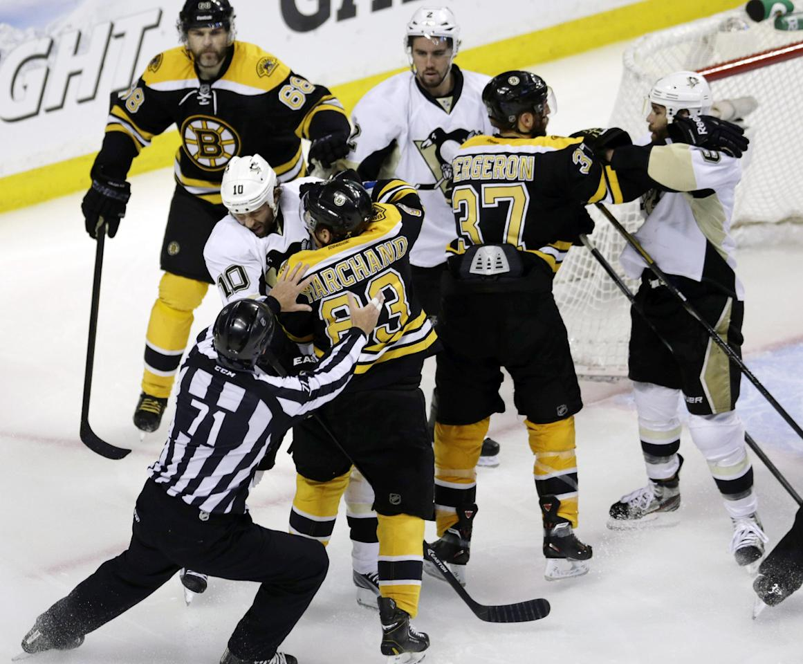 Linesman Brad Kovachik works to separate Pittsburgh Penguins left wing Brenden Morrow (10) and Boston Bruins left wing Brad Marchand (63) as they tangle in the second period of Game 4 in the Eastern Conference finals of the NHL hockey Stanley Cup playoffs, in Boston on Friday, June 7, 2013. (AP Photo/Charles Krupa)