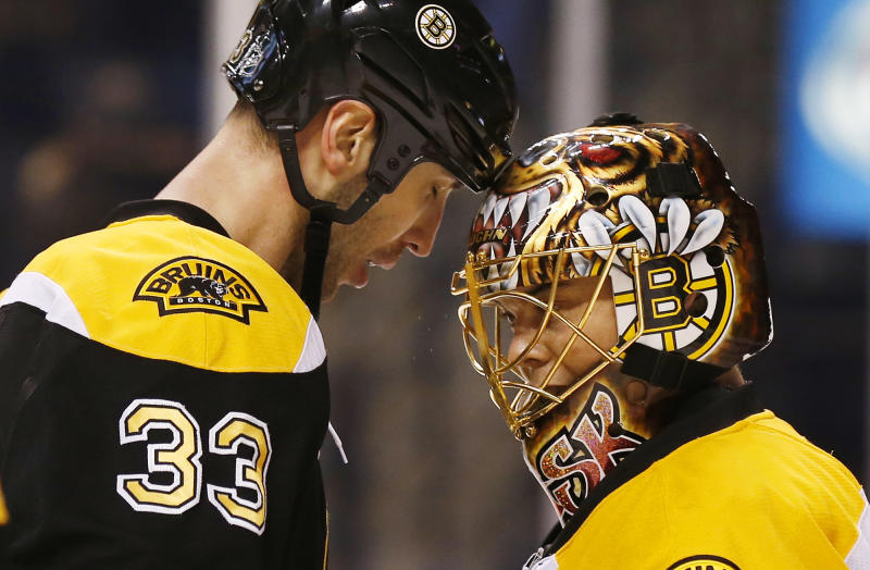Boston Bruins goalie Tuukka Rask of Finland is congratulated by defenseman Zdeno Chara (33) of Slovakia after their 2-1 win over the Phoenix Coyotes in an NHL hockey game in Boston Thursday, March 13, 2014