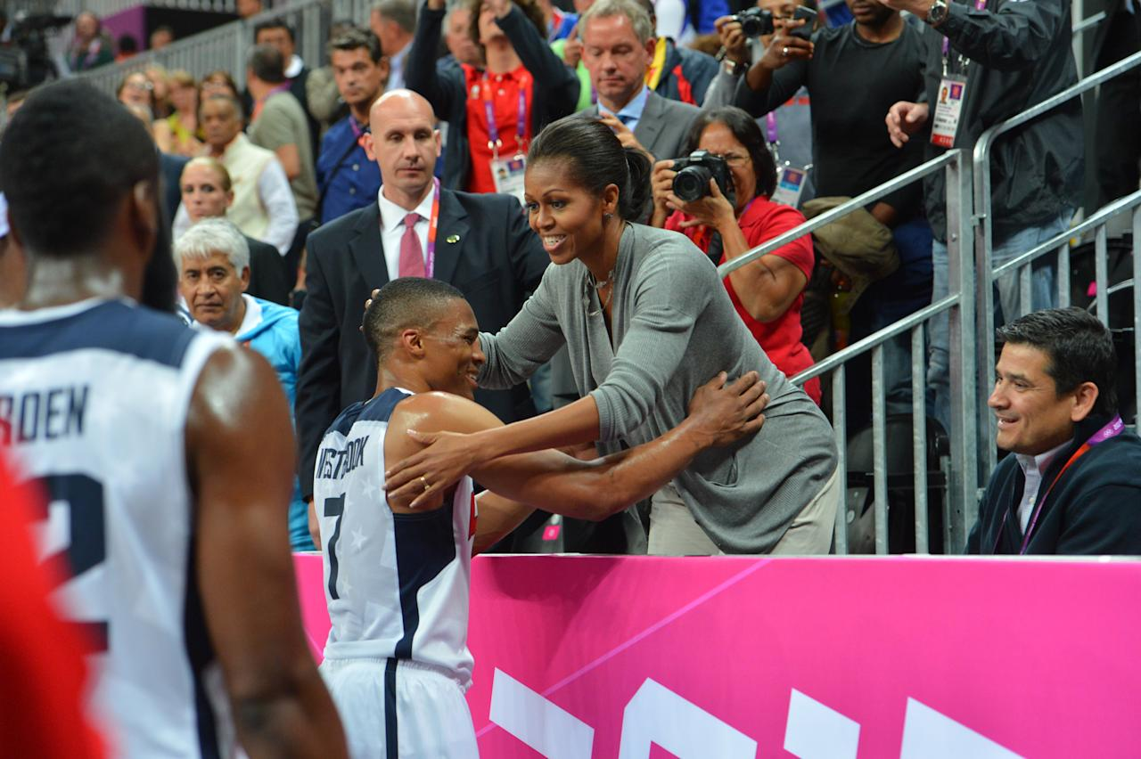 Russell Westbrook #7 of the USA Mens Senior National team hugs The First Lady Michelle Obama after defeating France 98-71 at the Olympic Park Basketball Arena during the London Olympic Games on July 29, 2012 in London, England. NOTE TO USER: User expressly acknowledges and agrees that, by downloading and/or using this Photograph, user is consenting to the terms and conditions of the Getty Images License Agreement. Mandatory Copyright Notice: Copyright 2012 NBAE (Photo by Jesse D. Garrabrant/NBAE via Getty Images)