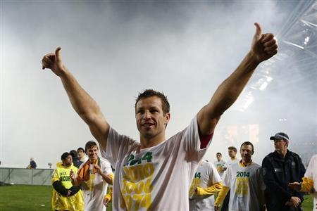 Australia's captain Neill celebrates after defeating Iraq to qualify for the 2014 FIFA World Cup, at Australia Stadium in Sydney