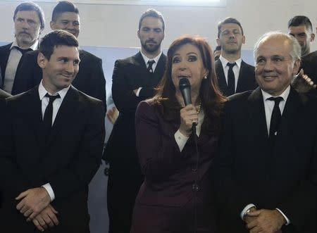 Argentine President Cristina Fernandez de Kirchner speaks next to soccer player Lionel Messi and coach Alejandro Sabella as Argentina's national soccer team arrives at the Argentine Football Association in Buenos Aires