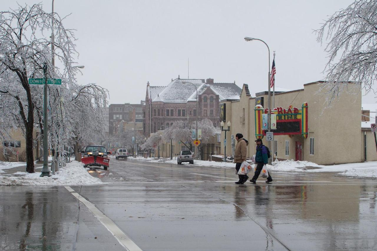 Two men haul food and toilet paper from a grocery store in downtown Sioux Falls, S.D., on Wednesday, April 10, 2013, as the city hunkered down for another stormy night. A spring storm that began Tuesday and was expected to last through Thursday wreaked havoc on roads, downed branches and knocked out power for thousands of residents. (AP Photo/Amber Hunt)