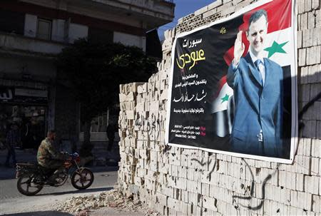 Man on a motorcycle rides past a poster depicting Syria's President Assad on a wall in the pro-government al-Zahraa neighbourhood in Homs