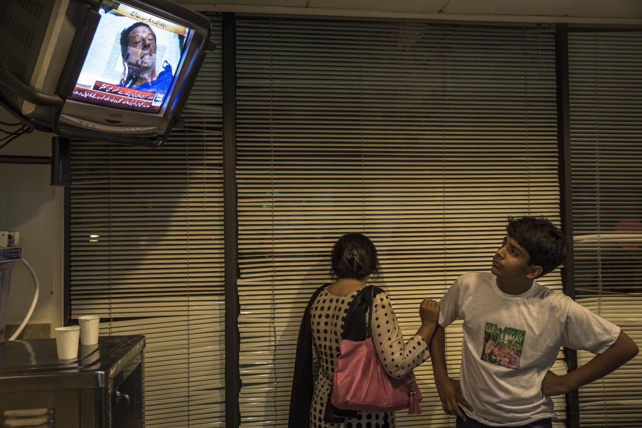 LAHORE, PAKISTAN - MAY 07: A woman turns away with grief as people watch a television in the foyer of Shaukat Khanum Memorial Cancer Hospital showing an interview with Imran Khan, chairman of the Pakistan Tehrik e Insaf (PTI) party, laying in intensive care and who is undergoing medical treatment, after he sustained an injury falling off a lifter during an election campaign rally on May 07, 2013 in Lahore, Pakistan. PTI chairman Imran Khan was injured at a rally in Lahore today after having fallen off a lifter. Pakistan's parliamentary elections are due to be held on May 11. Imran Khan of Pakistan Tehrik e Insaf (PTI) and Nawaz Sharif of the Pakistan Muslim League-N (PMLN) have been campaigning hard in the last weeks before polling. (Photo by Daniel Berehulak/Getty Images)
