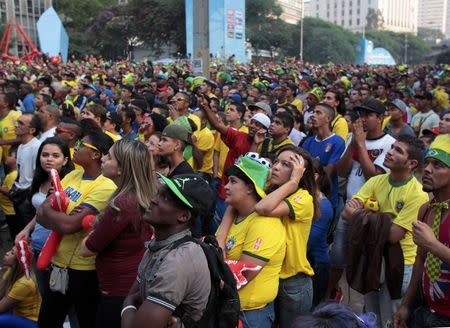 Soccer fans react while watching the 2014 World Cup Group A soccer match between Brazil and Mexico in Sao Paulo