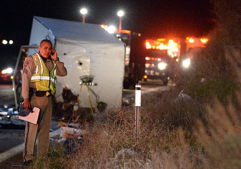 A California Highway Patrol officer stands near the crash scene where at least eight people were killed and nearly two dozen were injured when a bus carrying a group from Tijuana, Mexico crashed with two other vehicles on its way back from Big Bear Lake on Highway 38 north of Yucaipa, Calif., Sunday, Feb. 3, 2013. Both sides of the highway remained closed two and a half hours after the crash and it was unclear when it would reopen. (AP Photo/The Sun, Rick Sforza) MANDATORY CREDIT