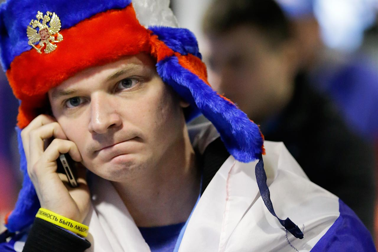 A Russia fan talks on his mobile phone as he leaves the areana after Russia's 3-1 loss to Finland during the men's quarterfinal hockey game in Bolshoy Arena at the 2014 Winter Olympics, Wednesday, Feb. 19, 2014, in Sochi, Russia. (AP Photo/David J. Phillip )