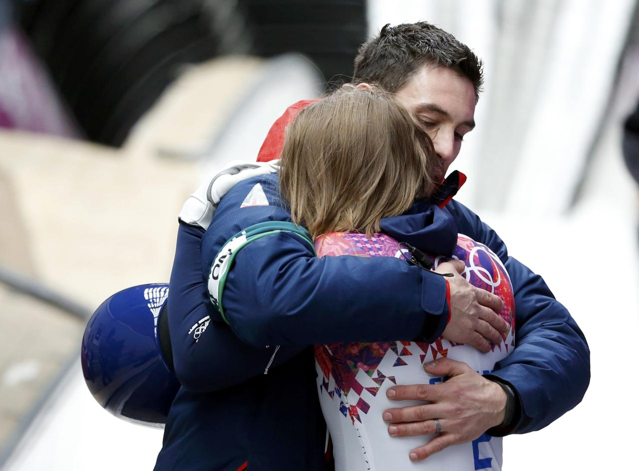 Britain's Elizabeth Yarnold celebrates with her coach after winning the women's skeleton event at the 2014 Sochi Winter Olympics February 14, 2014. REUTERS/Murad Sezer (RUSSIA - Tags: SPORT SKELETON OLYMPICS)