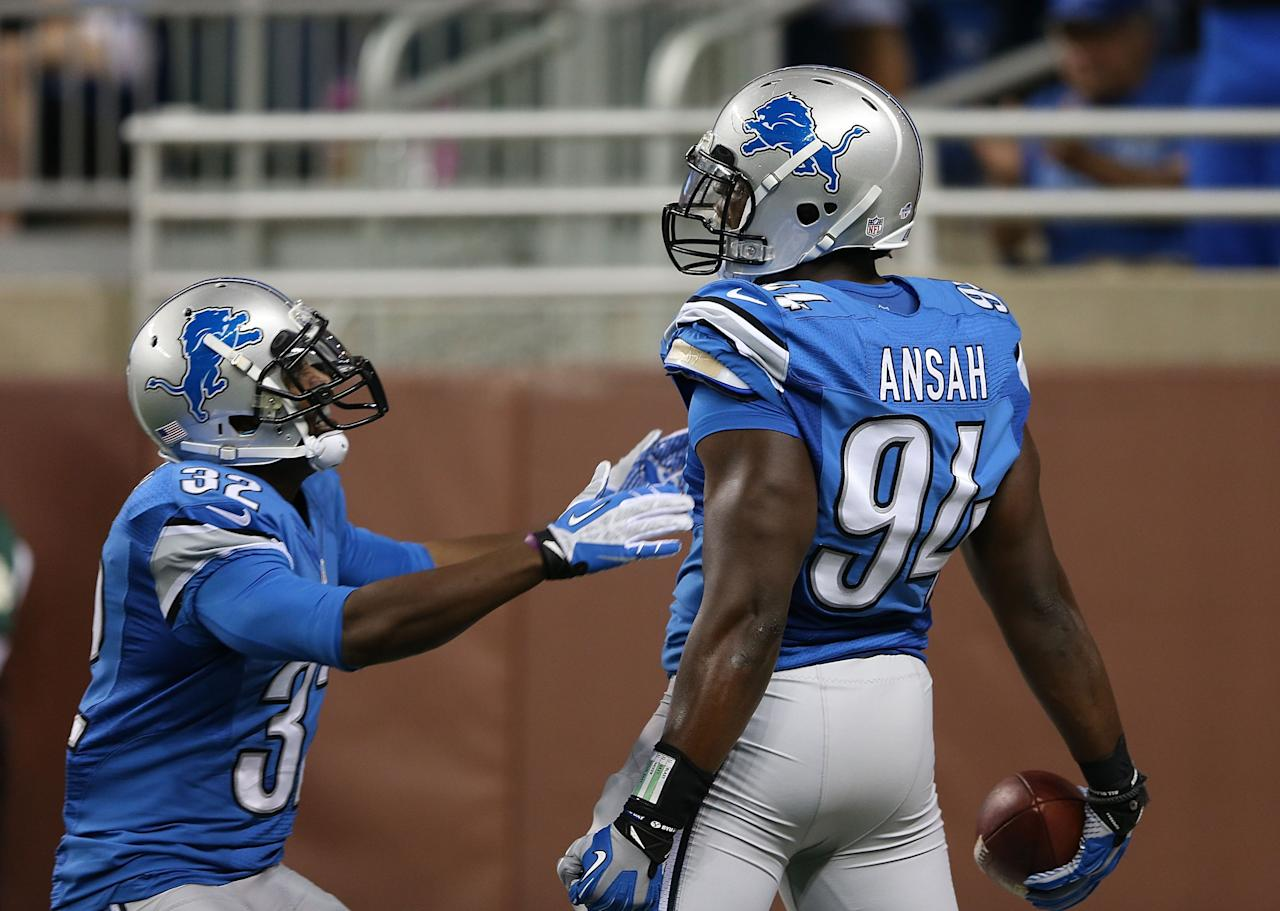DETROIT, MI - AUGUST 09: Ezekiel Ansah #94 of the Detroit Lions celebrates a first quarter touchdow with teammate Don Carey #32 after intercepting the pass from quarterback Mark Sanchez #6 of the New York Jets at Ford Field on August 9, 2013 in Detroit, Michigan. (Photo by Leon Halip/Getty Images)