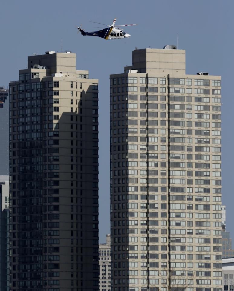 A New Jersey State Police helicopter flies over Jersey City, N.J., Monday, April 15, 2013. New Jersey is securing its city, which sits along the Hudson River across from New York City, in the wake of explosions near the finish line at the Boston Marathon. (AP Photo/Julio Cortez)