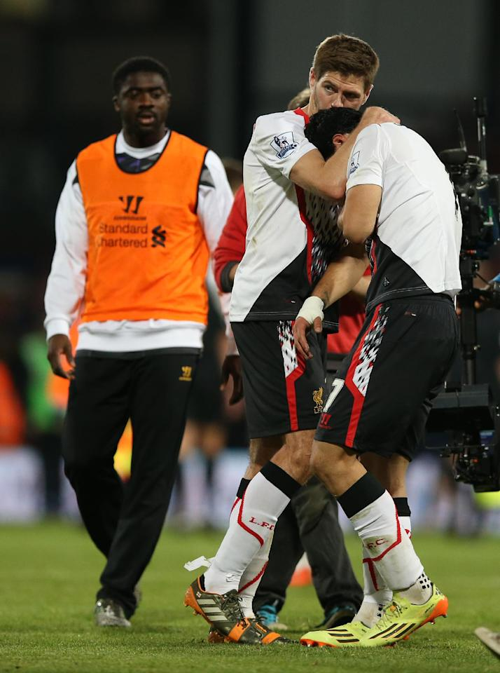 Liverpool's Steven Gerrard, centre, helps teammate Luis Suarez, following the end of the English Premier League soccer match between Crystal Palace and Liverpool at Selhurst Park stadium in London, Monday, May 5, 2014. The game ended in a 3-3 draw. (AP Photo/Alastair Grant)