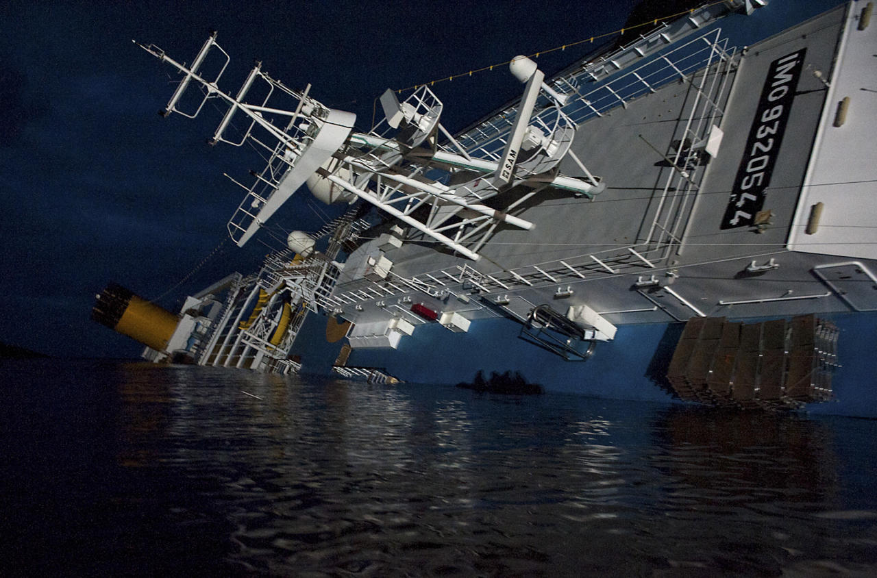 In this undated photo released by the Italian Navy Tuesday, Jan. 24, 2012, the Costa Concordia cruise ship grounded off the Tuscan island of Giglio, Italy, is seen at night. A large platform carrying a crane and other equipment hitched itself to the toppled Costa Concordia on Tuesday, signaling the start of preliminary operations to remove a half-million gallons of fuel from the grounded cruise ship before it leaks into the pristine Tuscan sea. Actual pumping of the oil isn't expected to begin until Saturday, but officials from the Dutch shipwreck salvage firm Smit were seen on the bow of the Concordia and in the waters nearby making preparations to remove the fuel, while the search for missing passengers continues. (AP Photo/Italian Navy GOS)
